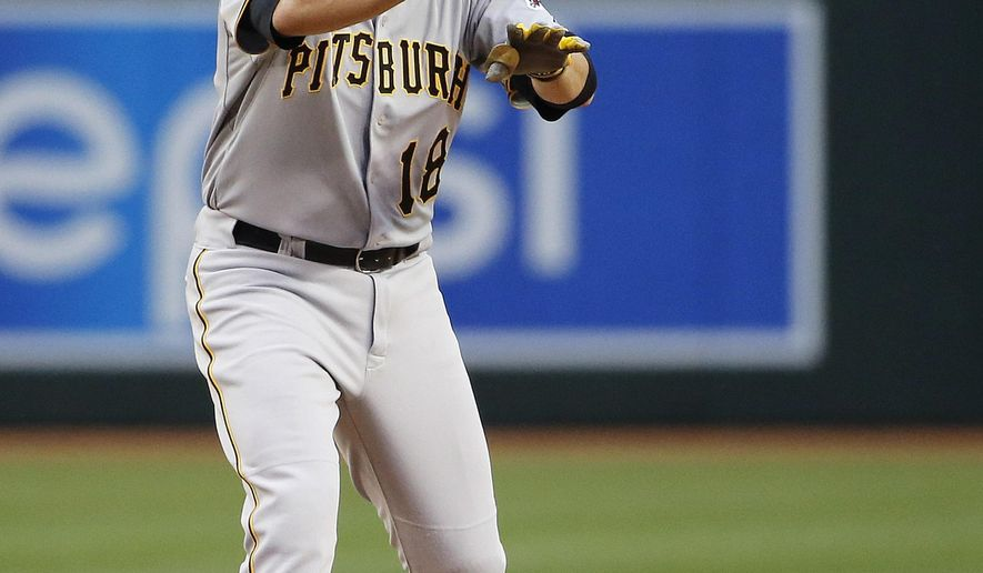 Pittsburgh Pirates' Neil Walker motions to teammates in the dugout after hitting a double against the Arizona Diamondbacks during the fourth inning of a baseball game Saturday, April 25, 2015, in Phoenix. (AP Photo/Ross D. Franklin)