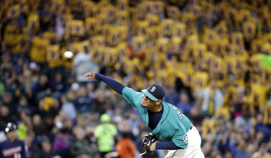 """Seattle Mariners starting pitcher Felix Hernandez throws, with a backdrop of yellow """"K"""" strikeout cards held by fans, during the fifth inning of the Mariners' baseball game against the Minnesota Twins on Friday, April 24, 2015, in Seattle. (AP Photo/Elaine Thompson)"""