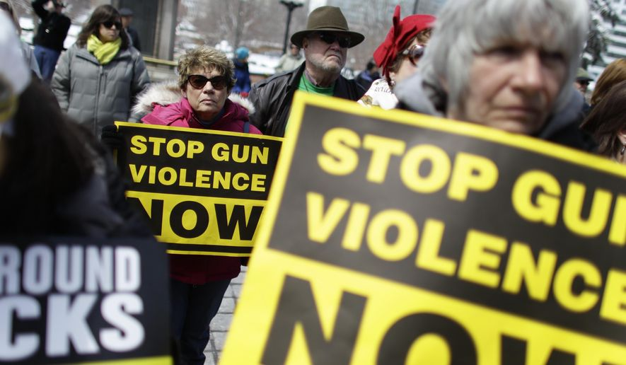 """FILE - In this April 18, 2013 file photo, community gun safety advocates and members of the public hold signs during a rally and vigil to honor victims of gun violence, sponsored by Colorado Ceasefire, on the steps of the Colorado State Capitol, in Denver. When a gunman opened fire inside a packed movie theater in July of 2012, killing 12, it helped revive the national debate over gun control. But, as the trial of theater shooter James Holmes is scheduled to begin Monday, April 27, 2015, Colorado's gun debate has quieted down. """"It's in a sort of gridlock,"""" said nonpartisan Denver pollster Floyd Ciruli. (AP Photo/Brennan Linsley, file)"""