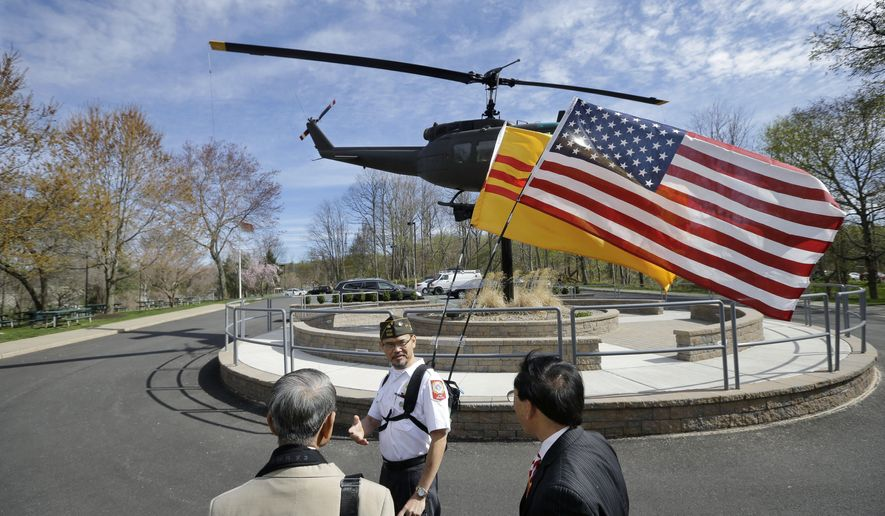 Du Hua bears America and South Vietnam flags as he walks near the display of a Vietnam era helicopter during ceremonies commemorating the 40th anniversary of Operation Babylift from Vietnam, Friday, April 24, 2015, in Holmdel, N.J. Du Hua, who took 11 attempts to escape from communist Vietnam, went on to serve in the U.S. Navy and is now a doctor of Pharmacy. (AP Photo/Mel Evans)