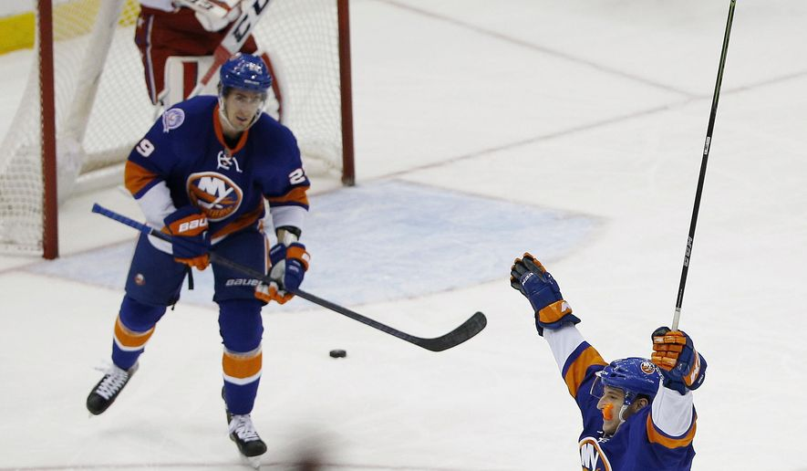 New York Islanders center Brock Nelson (29) and Ryan Strome, right, celebrate a first period goal by center John Tavares against the Washington Capitals during Game 6 during the first round of the NHL hockey Stanley Cup playoffs, Saturday, April 25, 2015, in New York. Strome had an assist on the goal. (AP Photo/Julie Jacobson)