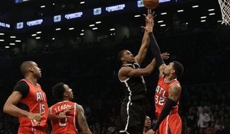 Brooklyn Nets forward Thaddeus Young goes to the basket past Atlanta Hawks forward Mike Scott (32) during the first half in Game 3 of a first-round NBA basketball playoff series, Saturday, April 25, 2015, at  New York.  Hawks Al Horford (15) and Jeff Teague (0) watch the action.(AP Photo/Mary Altaffer)