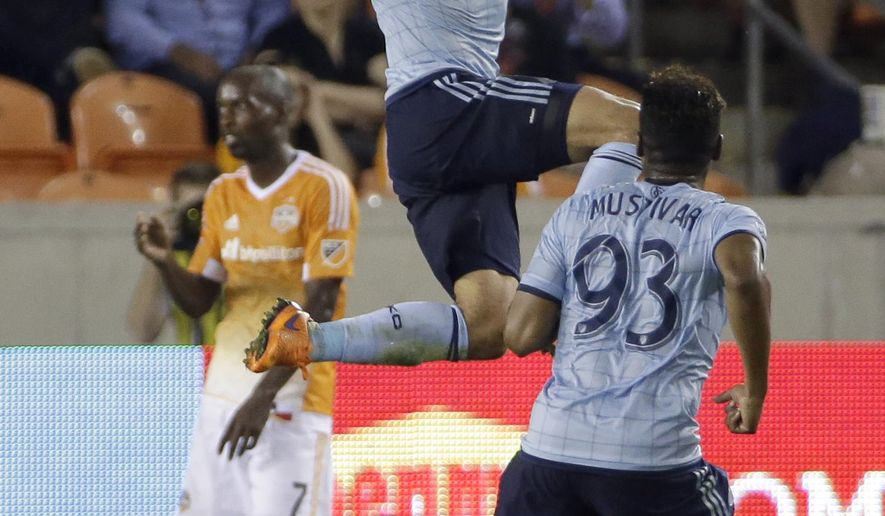 Sporting Kansas City's Benny Feilhaber, center, leaps after scoring the game-tying goal against the Houston Dynamo during the second half of an MLS soccer game Saturday, April 25, 2015, in Houston. Kansas City's Soni Mustivar (93 looks on. The teams tied 4-4. (AP Photo/David J. Phillip)