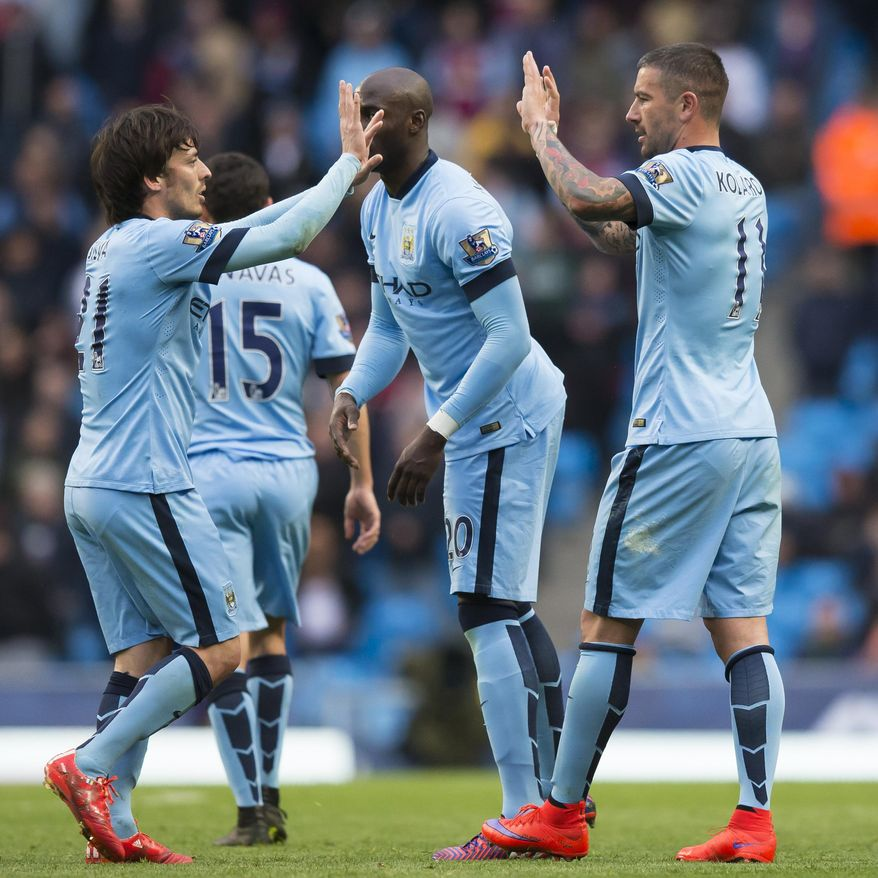Manchester City's Aleksandar Kolarov, right, celebrates with teammates after scoring from a free kick during the English Premier League soccer match between Manchester City and Aston Villa at the Etihad Stadium, Manchester, England, Saturday April 25, 2015. (AP Photo/Jon Super)