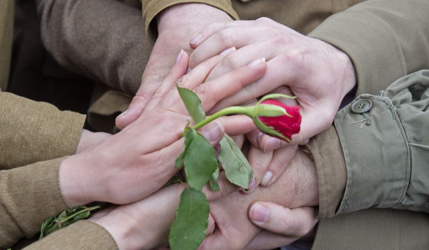 Amateur actors put their hands together during re-enacting the link-up of Soviet and American troops at the 70th anniversary of the Elbe Day in Torgau, eastern Germany, Saturday, April 25, 2015. The WW II link-up of US and Soviet Forces occurred here at the river Elbe on April 25, 1945. (AP Photo/Jens Meyer)