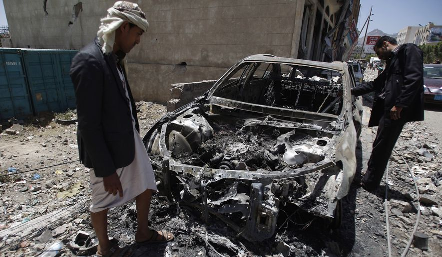 Men look at a car destroyed by a recent Saudi-led airstrike  in Yemen's capital, Sanaa,  Saturday, April 25, 2015.  With combatants fighting in neighborhoods and Saudi-led coalition warplanes pounding Iran-backed rebels from the sky, Yemen's war is wreaking a particularly bloody toll among civilians: more than 550 have been killed in the past month, including 115 children, the U.N. said Friday. (AP Photo/Hani Mohammed)