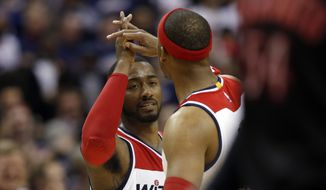 Washington Wizards guard John Wall (2) celebrates with forward Paul Pierce (34) during the second half of Game 3 in the first round of the NBA basketball playoffs against the Toronto Raptors, Friday, April 24, 2015, in Washington. The Wizards won 106-99. (AP Photo/Alex Brandon)