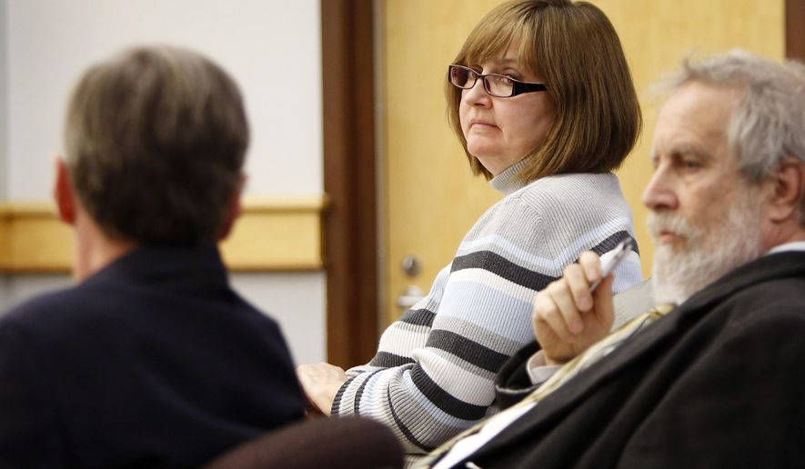 FILE - In a Thursday Dec. 18, 2014 file photo, former family practice doctor Genevieve Kelley, center, looks back at her lawyers during a hearing in Coos County Superior Court in Lancaster, N.H. Kelley is charged with fleeing the country with her young daughter during a custody dispute.  Kelley, turned herself in to face a custodial interference charge. (AP Photo/Jim Cole, File)