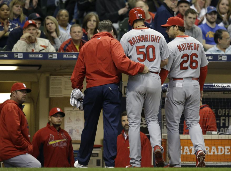 St. Louis Cardinals starting pitcher Adam Wainwright (50) is helped off the field after getting injured while batting during the fourth inning of a baseball game against the Milwaukee Brewers Saturday, April 25, 2015, in Milwaukee.  (AP Photo/Jeffrey Phelps)