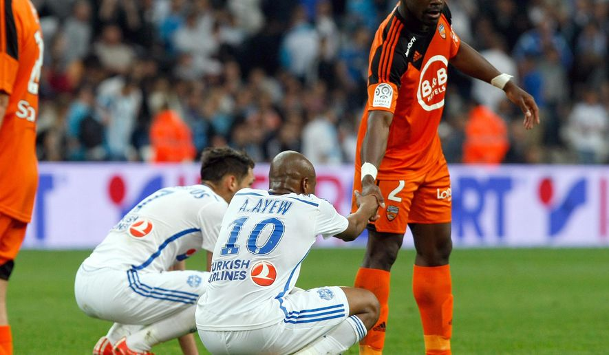 Marseille's Ghanaian forward Andre Ayew, center, shakes hands with Lorient's French defender Lamine Kone at the end of  the League One soccer match between Marseille and Lorient, at the Velodrome Stadium, in Marseille, southern France, Friday, April 24, 2015. Lorient won 5-3.  (AP Photo/Claude Paris)