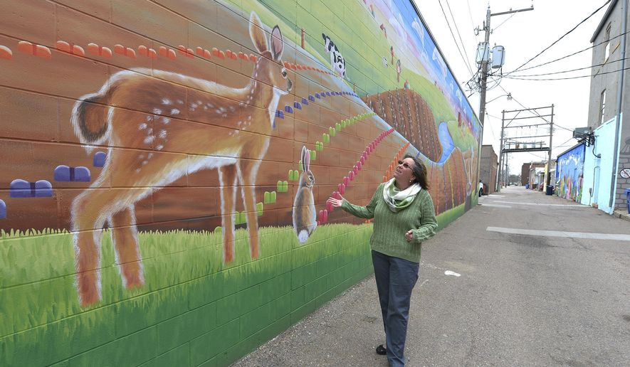 Le Mars artist Jean Weiner talks about her mural, Home Grown, displayed  in an alley on April 15, 2015 in Le Mars, Iowa. Home Grown features ice cream novelties growing out of a farm field. The mural is part of an ongoing project to add art to the city's downtown alleys.  (Tim Hynds/The Sioux City Journal via AP)