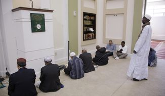 Muslim men gather early before a call to prayers in the mosque at the Islamic Society of Boston Cultural Center Friday, April 24, 2015, in Boston. (Associated Press)