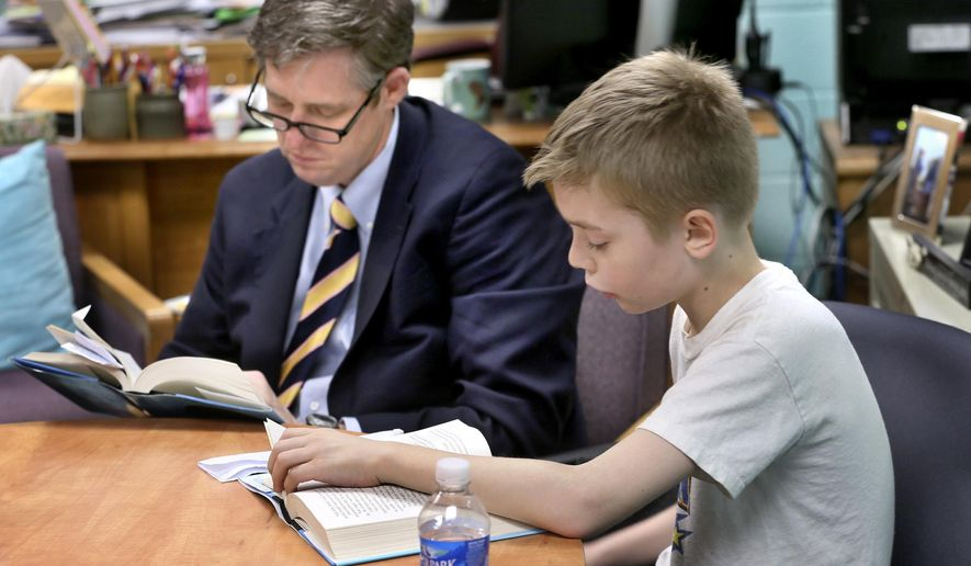 """Winchester Public Schools Superintendent Mark Lineburg, left, reads along as Frederick Douglass Elementary School fourth-grader Ryan Keck reads aloud from """"Wonder,"""" at Frederick Douglas Elementary School on Friday, April 17, 2015 in Winchester, Va.  The book focuses on the story of a fifth-grade boy who is born with a facial deformity.  Lineburg  said the premise behind the book is that when choosing between doing something right or doing something kind, one should always choose to do something kind.  (Ginger Perry/The Winchester Star via AP)"""
