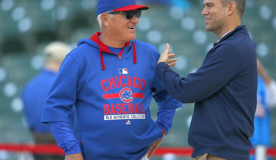 FILE - In this April 13, 2015, file photo, Theo Epstein, right, Chicago Cubs president of baseball operations, talks with Cubs manager Joe Maddon during batting practice before the Cubs' baseball game against the Cincinnati Reds in Chicago. With runs at a premium in the major leagues, a handful of teams are trying to help their young hitters with a high-tech program known as neuroscouting. The details are being treated as a state secret by three clubs believed to be using the product--the Cubs, Red Sox and Rays. (AP Photo/Jeff Haynes, File)