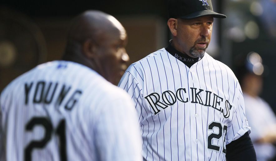 Colorado Rockies manager Walt Weiss, back, confers with first base coach Eric Young during the fifth inning of the team's baseball game against the San Francisco Giants on Saturday, April 25, 2015, in Denver. (AP Photo/David Zalubowski)
