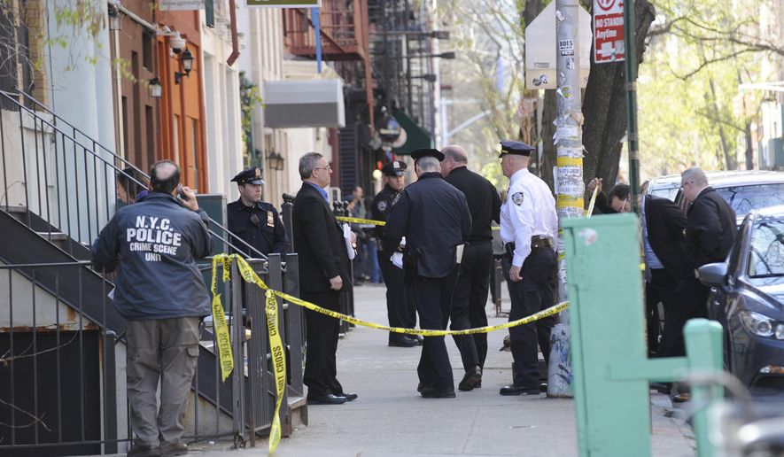 Police personnel gather at the scene of a police shooting on 6th street in the East Village, Saturday, April, 2015, in New York. (AP Photo/ Louis Lanzano)