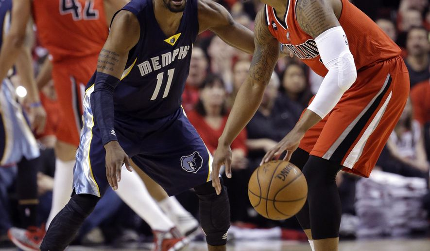 Portland Trail Blazers guard Damian Lillard, right, dribbles against Memphis Grizzlies guard Mike Conley during the first half of Game 3 of a first-round NBA basketball playoff series in Portland, Ore., Saturday, April 25, 2015. (AP Photo/Don Ryan)