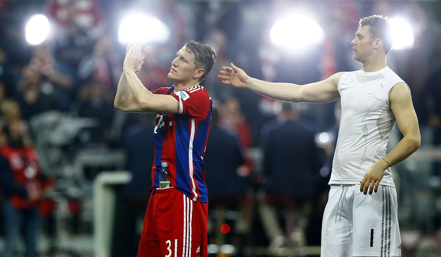 Bayern's Bastian Schweinsteiger, left, and goalkeeper Manuel Neuer applause to supporters after the German first division Bundesliga soccer match between FC Bayern Munich and Hertha BSC at the Allianz Arena in Munich, Germany, on Saturday, April 25, 2015. (AP Photo/Matthias Schrader)