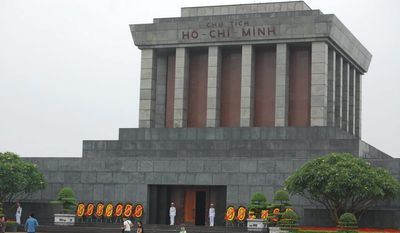 Ho Chi Minh's name, chiseled above the massive tomb's portico, shines red because of ruby-filled letters.