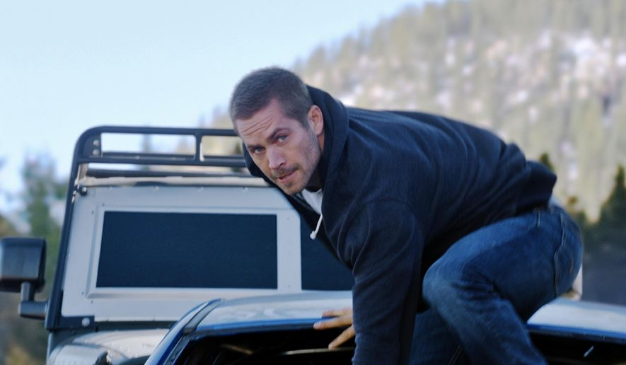 """FILE - This undated file photo provided by Universal Pictures shows, Paul Walker as Brian, in a scene from """"Furious 7.""""  """"Furious 7"""" topped """"Age of Adaline"""" and lead the box office for a fourth straight week. The Universal action film made an estimated $18.3 million in North American theaters over the weekend, according to studio estimates Sunday, April 26, 2015. (AP Photo/Universal Pictures, File)"""