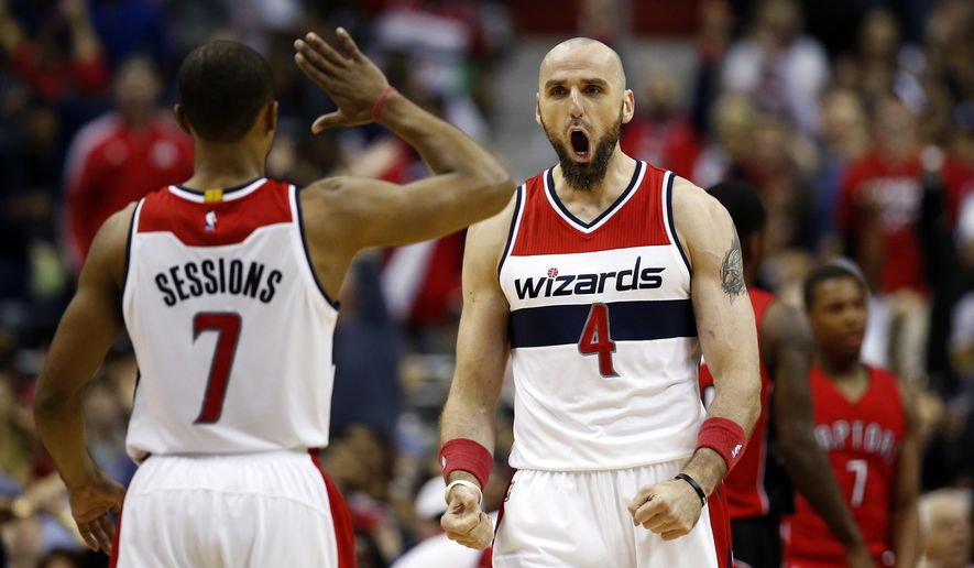 Washington Wizards guard Ramon Sessions (7) and center Marcin Gortat (4), from Poland, celebrate after a play in the first half of Game 4 in the first round of the NBA basketball playoffs against the Toronto Raptors, Sunday, April 26, 2015, in Washington. (AP Photo/Alex Brandon)