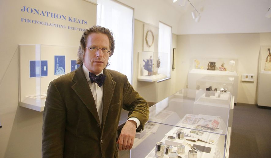 """Jonathon Keats poses in his """"millennium camera"""" exhibit at the Mead Art Museum on the Amherst College campus Thursday, April 16, 2015, in Amherst, Mass. Keats, a San Francisco-based writer who describes himself as an experimental philosopher and conceptual artist, has designed a camera he plans to perch atop a church-less steeple on the Amherst College campus, hoping the device will chronicle climate change by making a 1,000-year-long photograph of the Holyoke Range in western Massachusetts. (AP Photo/Stephan Savoia)"""