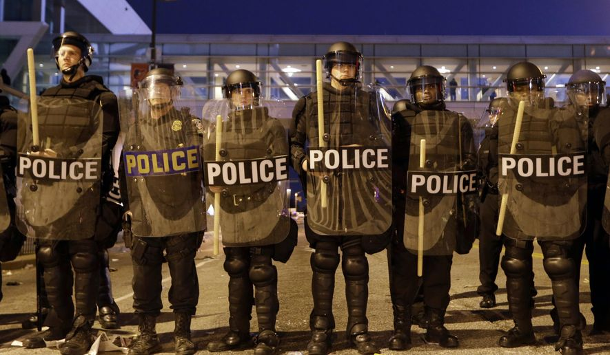 Police line a street in downtown Baltimore in response to protests that followed a rally for Freddie Gray, Saturday, April 25, 2015. Gray died from spinal injuries about a week after he was arrested and transported in a police van. (AP Photo/Patrick Semansky)