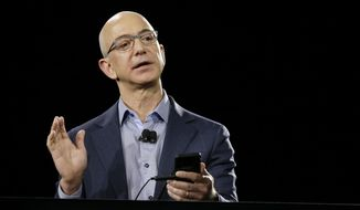 Amazon CEO Jeff Bezos demonstrates the new Amazon Fire Phone during a launch event, in Seattle, in this June 18, 2014, file photo. (AP Photo/Ted S. Warren, File)
