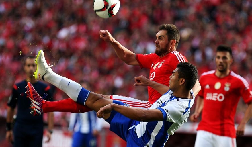 Porto's Carlos Casemiro, from Brazil, battles for the ball with Benfica's Jardel Vieira, top, also from Brazil, during the Portuguese league soccer match between Benfica and Porto at Benfica's Luz stadium, Sunday, April 26, 2015, in Lisbon, Portugal. The match ended in a 0-0 draw and Benfica leads the competition with three points ahead second placed Porto. (AP Photo/Francisco Seco)