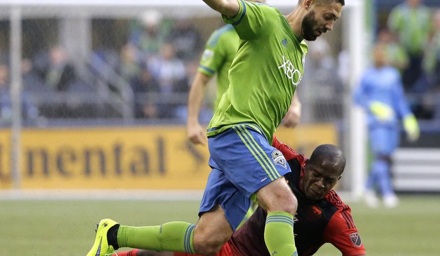 Seattle Sounders' Clint Dempsey runs with the ball as Portland Timbers' Darlington Nagbe goes down in the first half of an MLS soccer match, Sunday, April 26, 2015, in Seattle. (AP Photo/Ted S. Warren)