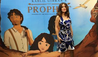 "Mexican-American actress Salma Hayek poses for photographers next to a poster for the film ""The  Prophet,"" an animated feature film she co-produced, on her arrival to a cinema where she gave a press conference, in Beirut, Lebanon, Monday, April 27, 2015. In her first visit to her ancestral homeland, Ms. Hayek, whose paternal grandfather was Lebanese and immigrated to Mexico, visited the picturesque mountain village of Bcharre in northern Lebanon on Sunday to pay homage to Khalil Gibran, the Lebanese-born poet who wrote ""The Prophet,"" the book on which the film is based. (AP Photo/Hussein Malla)"
