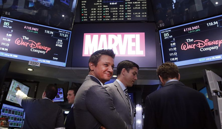 """Actor Jeremy Renner stands on the floor of the New York Stock Exchange after ringing the opening bell with his """"The Avengers: Age of Ultron"""" co-star Robert Downey Jr. and representatives from Marvel Entertainment, Monday, April 27, 2015, in New York. (AP Photo/Jason DeCrow)"""