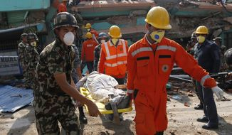 Rescue teams carry a body dug out of the collapsed Sitapyla church in Kathmandu, Nepal, Monday, April 27, 2015. A strong magnitude 7.8 earthquake shook Nepal's capital and the densely populated Kathmandu Valley on Saturday, causing extensive damage with toppled walls and collapsed buildings. (AP Photo/Wally Santana)