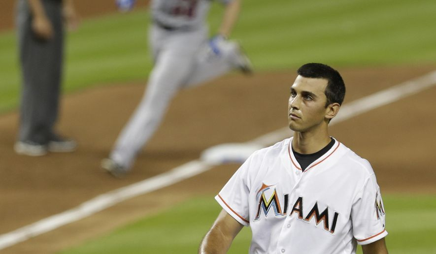 Miami Marlins relief pitcher Steve Cishek, right, looks up as New York Mets' Daniel Murphy (28) rounds third base after hitting a three-run home run against Cishek in the ninth inning of a baseball game, Monday, April 27, 2015, in Miami. The Mets won 3-1. (AP Photo/Alan Diaz)