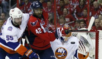New York Islanders defenseman Johnny Boychuk (55) defends as Washington Capitals right wing Joel Ward (42) attempts to deflect the shot against goalie Jaroslav Halak (41), from the Czech Republic, during the first period of Game 7 in the first round of the NHL hockey Stanley Cup playoffs, Monday, April 27, 2015, in Washington. (AP Photo/Alex Brandon)