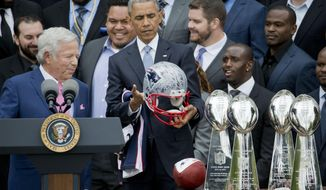 President Barack Obama looks over a signed New England Patriots football helmet presented to him by New England Patriots owner Robert Kraft, left, during a ceremony on the South Lawn of the White House in Wasington, Thursday, April 23, 2015, where the president honored the Super Bowl Champion New England Patriots for their Super Bowl XLIX victory. (AP Photo/Pablo Martinez Monsivais)