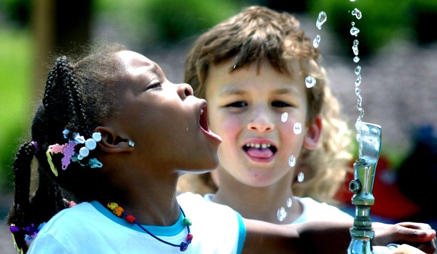 Tianna Swisher, a student at Liberty Valley Elementary School in Danville, Pa., attempts to drink from the water fountain at Montour Preserve near Washingtonville, Pa., during an outdoor field trip. (Associated Press)