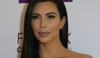 """FILE - In a Wednesday, April 15 2015 file photo, Kim Kardashian attends a photocall to launch hair products in Paris. Kardashian said during an appearance on NBC's """"Today"""" show on Monday, April 27, 2015, that she and her family support her stepfather Bruce Jenner 100 percent as he goes through gender transition, even though family members are still adjusting to that news in what she called """"a daily process.""""(AP Photo/Jacques Brinon, File)"""