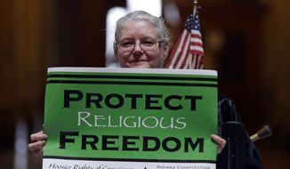 Condy Holmes of Mechanicsburg, Ind., holds a sign a rally at the Statehouse in Indianapolis, Monday, April 27, 2015, against the revised religious freedom legislation. (AP Photo/Michael Conroy) ** FILE **