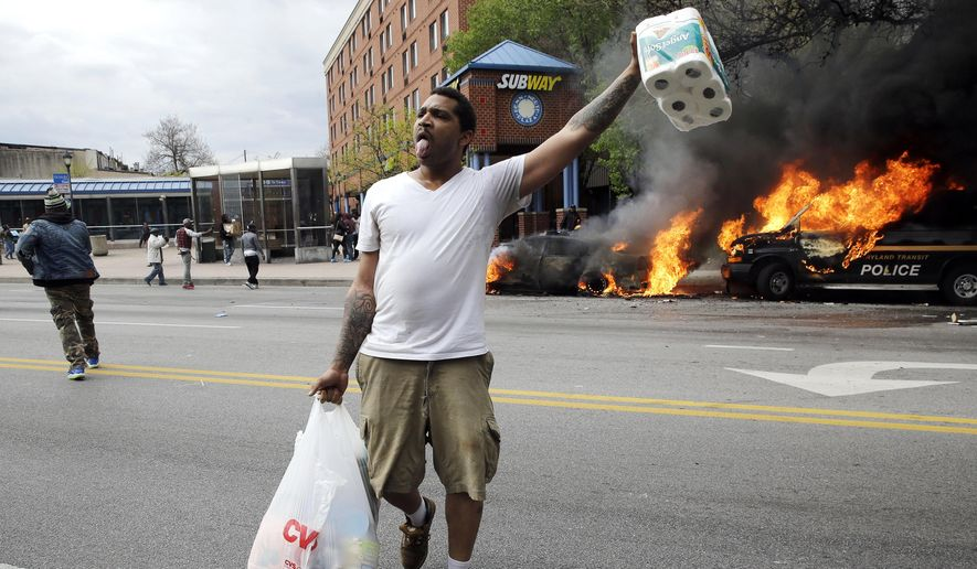 A man carries items from a store as police vehicles burn, Monday, April 27, 2015, after the funeral of Freddie Gray in Baltimore. Gray died from spinal injuries about a week after he was arrested and transported in a Baltimore Police Department van. (AP Photo/Patrick Semansky)