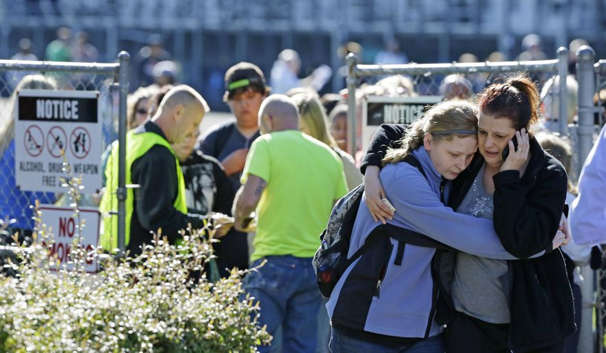 Parents and students walk away from an area at North Thurston High School Monday, April 27, 2015, where students were released to their parents after a shooting at the school earlier in the morning. Police say no one was injured, and school district officials say the gunman has been apprehended by staff. (AP Photo/Ted S. Warren)
