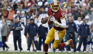 Washington Redskins quarterback Robert Griffin III (10) scrambles with the ball during the first half of an NFL football game against the Dallas Cowboys in Landover, Md., Sunday, Dec. 28, 2014. (AP Photo/Alex Brandon)