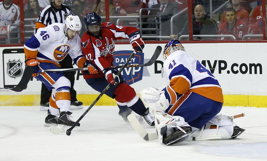 Washington Capitals right wing Joel Ward (42) tries to shoot against New York Islanders defenseman Matt Donovan (46) and goalie Jaroslav Halak (41), from the Czech Republic, during the first period of Game 7 in the first round of the NHL hockey Stanley Cup playoffs, Monday, April 27, 2015, in Washington. (AP Photo/Alex Brandon)
