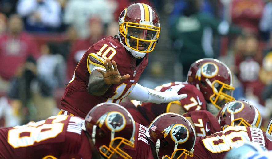 FILE - In this Dec. 28, 2014, file photo, Redskins quarterback Robert Griffin III yells prior to the snap of the ball during their NFL football game against the Dallas Cowboys in Landover, Md. Robert Griffin III's fifth-year contract option for the 2016 season will be exercised by the Washington Redskins. New general manager Scot McCloughan made the announcement at the beginning of his news conference Monday, April 27, 2015, to discuss the upcoming draft, which begins Thursday night. (AP Photo/Richard Lipski, File)