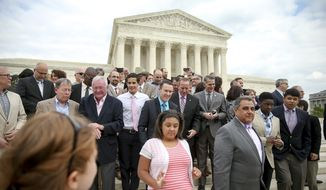 Plaintiffs from Tennessee, Michigan, and Ohio walk down steps at the Supreme Court  after posing for photographs with the lawyers representing in Washington, Monday, April 27, 2015, as the Supreme Court is scheduled to hear arguments on the constitutionality of state bans on same-sex marriage on Tuesday. (AP Photo/Andrew Harnik)