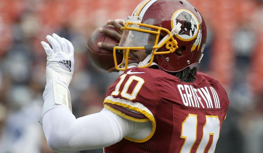 In this photo taken Dec. 28, 2014, Washington Redskins quarterback Robert Griffin III (10) warms up before an NFL football game against the Dallas Cowboys in Landover, Md. Griffin fifth-year contract option for the 2016 season will be exercised by the Washington Redskins. New general manager Scot McCloughan says the team will submit the proper paperwork to the NFL by next week's deadline. (AP Photo/Alex Brandon)