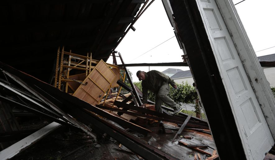 Meljen Portillo climbs over debris as he retrieves tools from the house he was working on when it collapsed around him Monday, April 27, 2015, in New Orleans. High winds blew rail cars off the Huey P. Long Bridge and nearly 250,000 homes and businesses lost power Monday morning as a line of severe thunderstorms moved across southeast Louisiana. (AP Photo/Butch Dill)