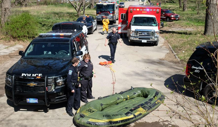 In this photo taken Monday, April 27, 2015, rescue vehicles block a Mason City, Iowa street, after two men were towed to safety from the Winnebago River. Police say the men's raft, pictured, became stuck near a dam south of 12th Street Northeast. Authorities say 26-year-old Rusty Thorngren and 45-year-old Marc Ciska were cited for public intoxication.  (Molly Montag/Globe-Gazette via AP)