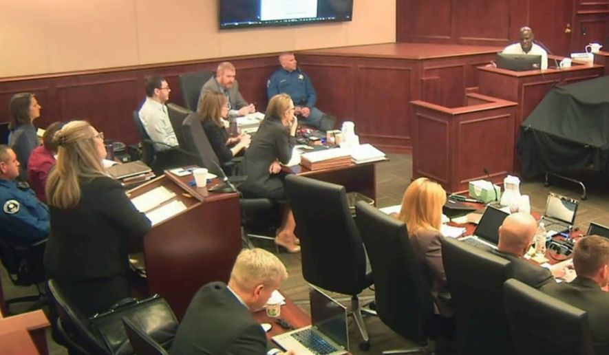 Colorado theater shooter James Holmes, left rear in light-colored shirt, watches during testimony by witness Derick Spruel, upper right, on the second day of his trial in Centennial, Colo., Monday, April 27, 2015. Standing at left is prosecutor Lisa Teesch-Maguire. (Colorado Judicial Department via AP, Pool)