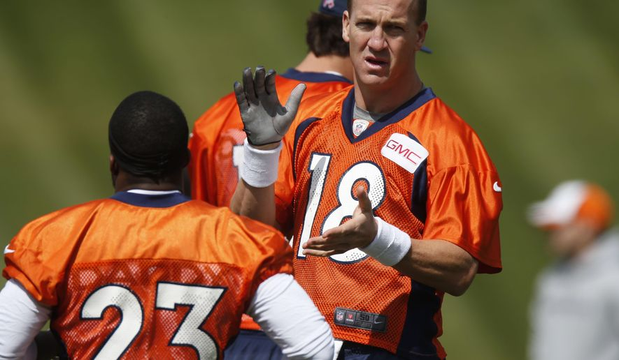 Denver Broncos quarterback Peyton Manning, back, claps as running back Ronnie Hillman takes part in drills during the NFL football team's voluntary veterans minicamp Tuesday, April 28, 2015, in Englewood, Colo. (AP Photo/David Zalubowski)